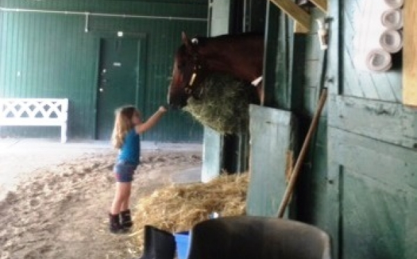 Mucho Macho Man with little girl in barn